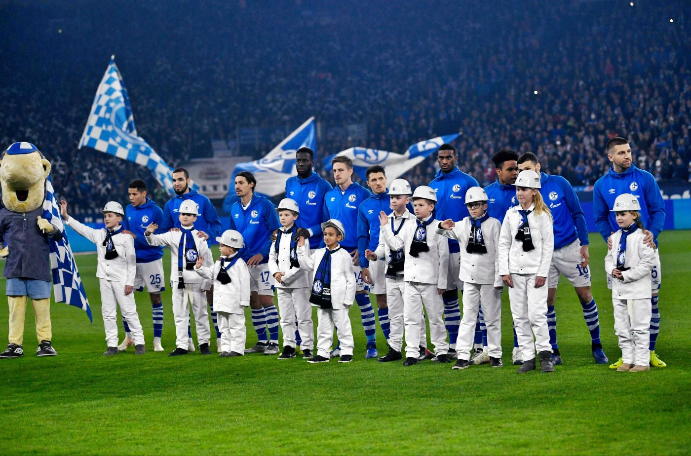 -- Schalke's players stand behind player escorts wering miner's clothes ahead of the German first division football match between FC Schalke 04 and Bayer Leverkusen on December 19, 2018. When Germany's last black coal mine shutters on December 21, 2018, it's not just workers who may shed a tear -- football fans too will mourn the end of the over 150-year-old industry. The industrial Ruhr region -- rich in coal, the blood and soul of industrial Germany since the 19th century -- is also the gritty home turf of some of Germany's best-loved football clubs. - Germany OUT / DFL REGULATIONS PROHIBIT ANY USE OF PHOTOGRAPHS AS IMAGE SEQUENCES AND/OR QUASI-VIDEO / AFP / dpa / Ina Fassbender / DFL REGULATIONS PROHIBIT ANY USE OF PHOTOGRAPHS AS IMAGE SEQUENCES AND/OR QUASI-VIDEO